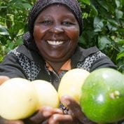 Woman smiling with hands full of produce