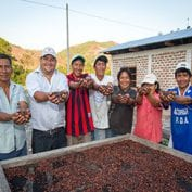 Group of people smiling holding up cocoa beans