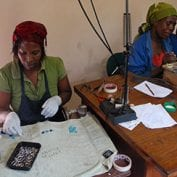 Group of women working to create jewelry
