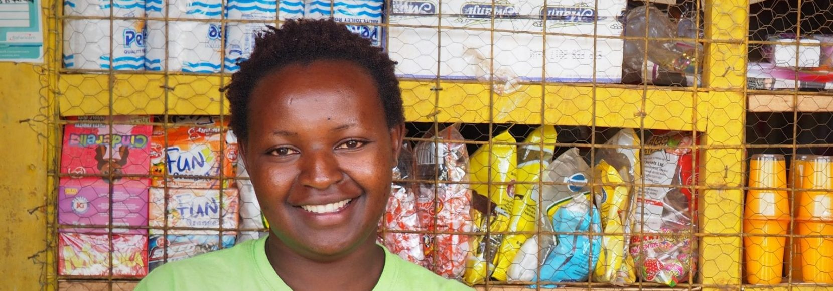 Woman smiling in front of food in Kenya