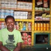 Woman smiling in front of food in Kenya