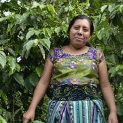 Woman smiling in front of coffee trees in Guatemala