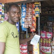 Man smiling in front of a Nigerian mom and pop shop