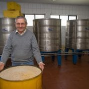 Man smiling in Chile with bin of grain