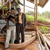 Two men working while inspecting a book