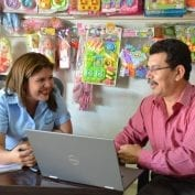 Small business owners smiling while looking at computer
