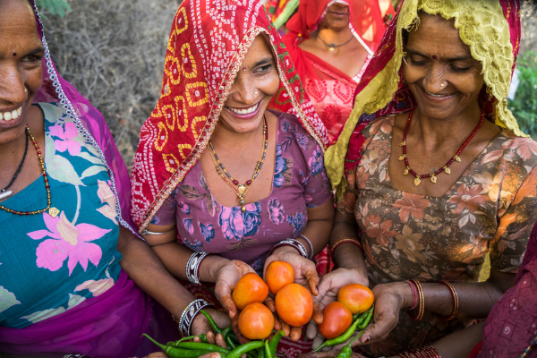 Women farmers in India holding produce despite the effects of climate change
