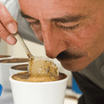 Man smelling and inspecting coffee in cup