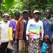 Family smiling surrounded by coffee trees
