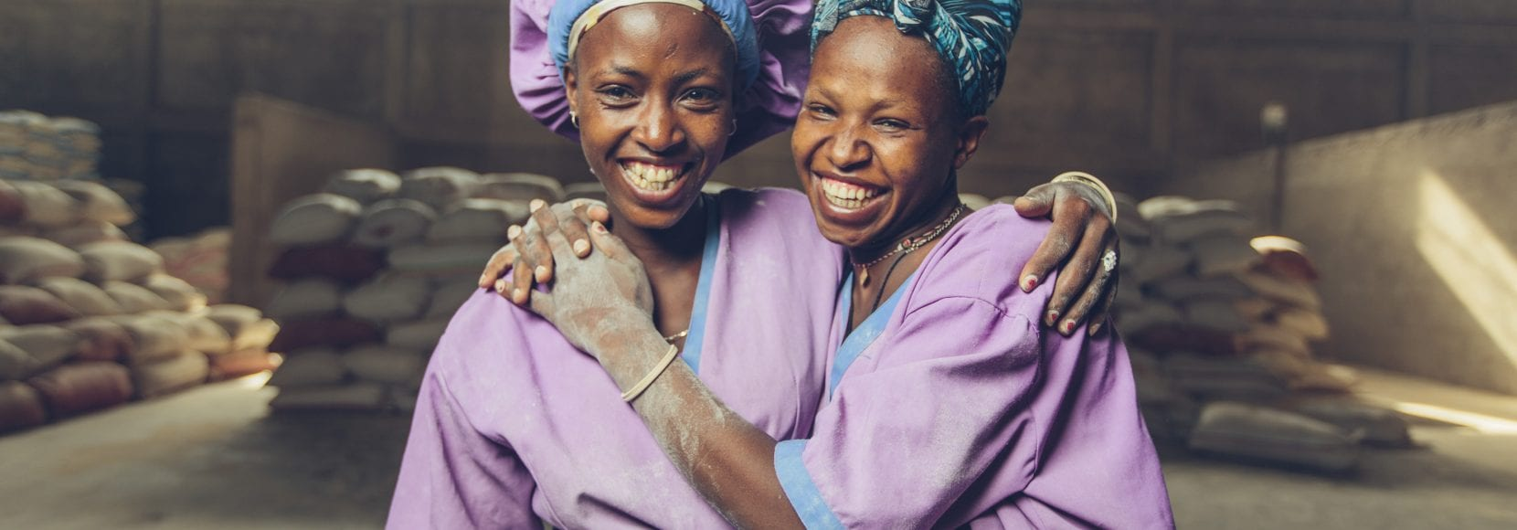 Women workers smiling at a grain mill in Sannie, Ethiopia