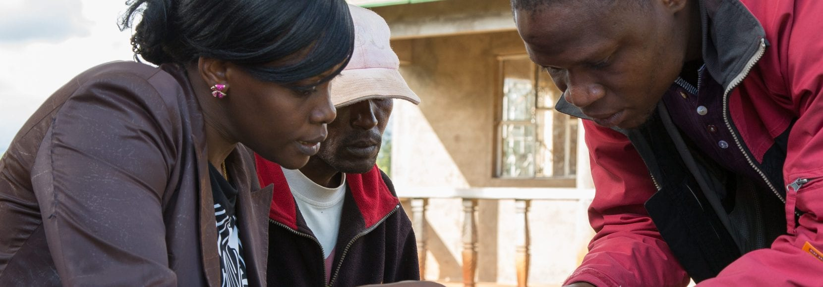 Careers at TechnoServe hero image - Farmers in Tanzania working with a consultant on record-keeping.