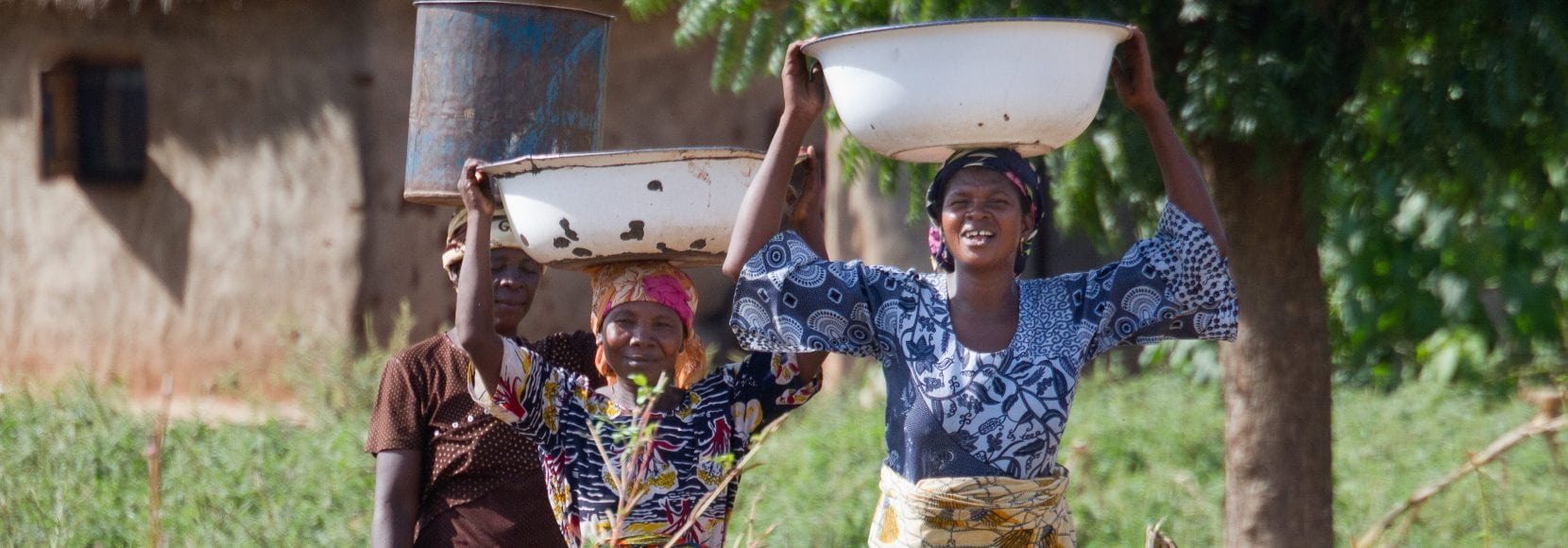 Sanatu Andani, 49, Mariama Andani, Damata Shihadu, 39 (left to right), carrying water from tap for Nyebu Be Yoona Shea Butter Processing Group, Kanfiehiyili village, Tamale, Ghana.