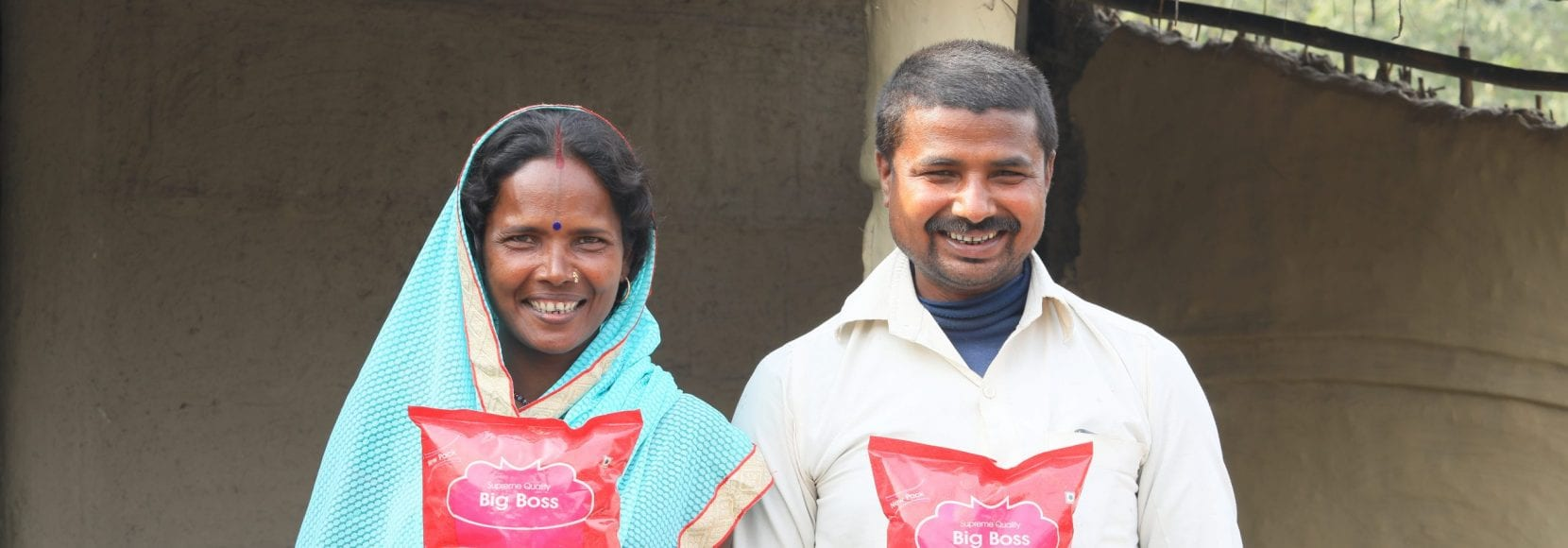 Smiling couple holding food up