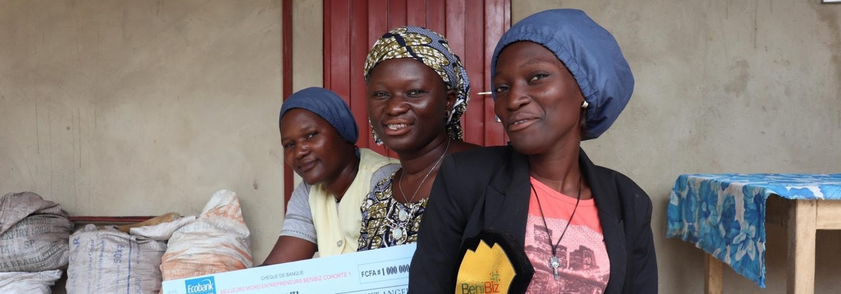 Three women in Benin smiling after receiving awards