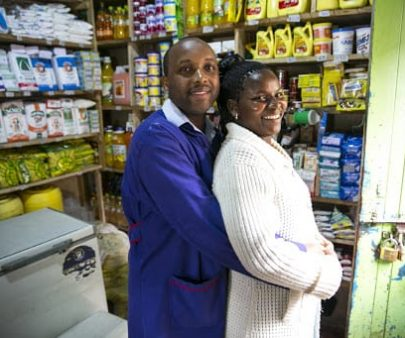 Smiling couple standing in their grocery store