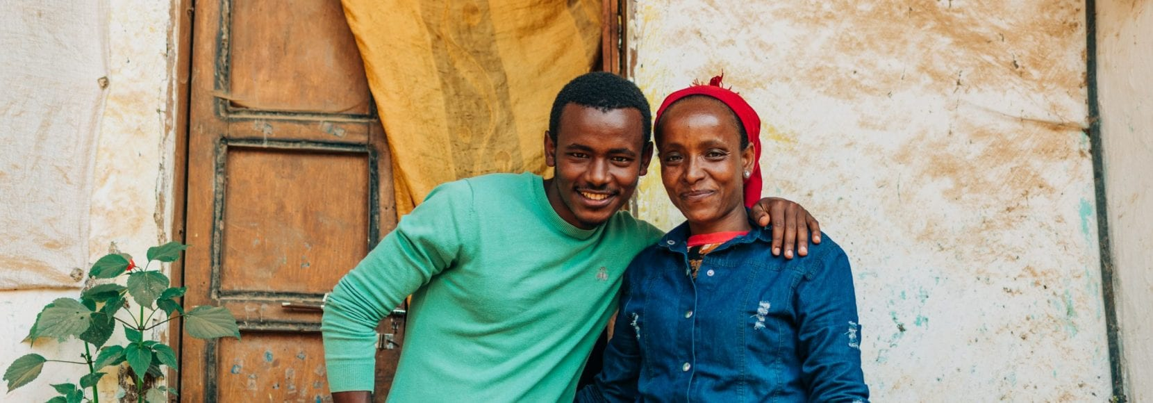 The impact of coffee has transformed what life looks like for Lubaba and her son smiling in front of their home