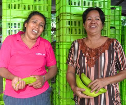 Two smiling women holding fruit