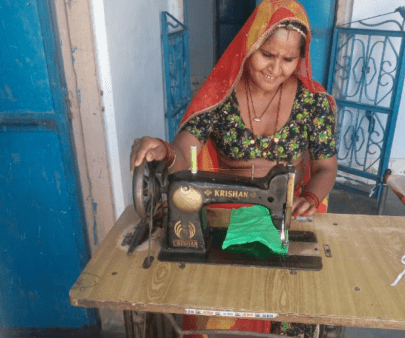 Our commitment to fighting poverty helps farmers in India like this woman making masks for COVID-19