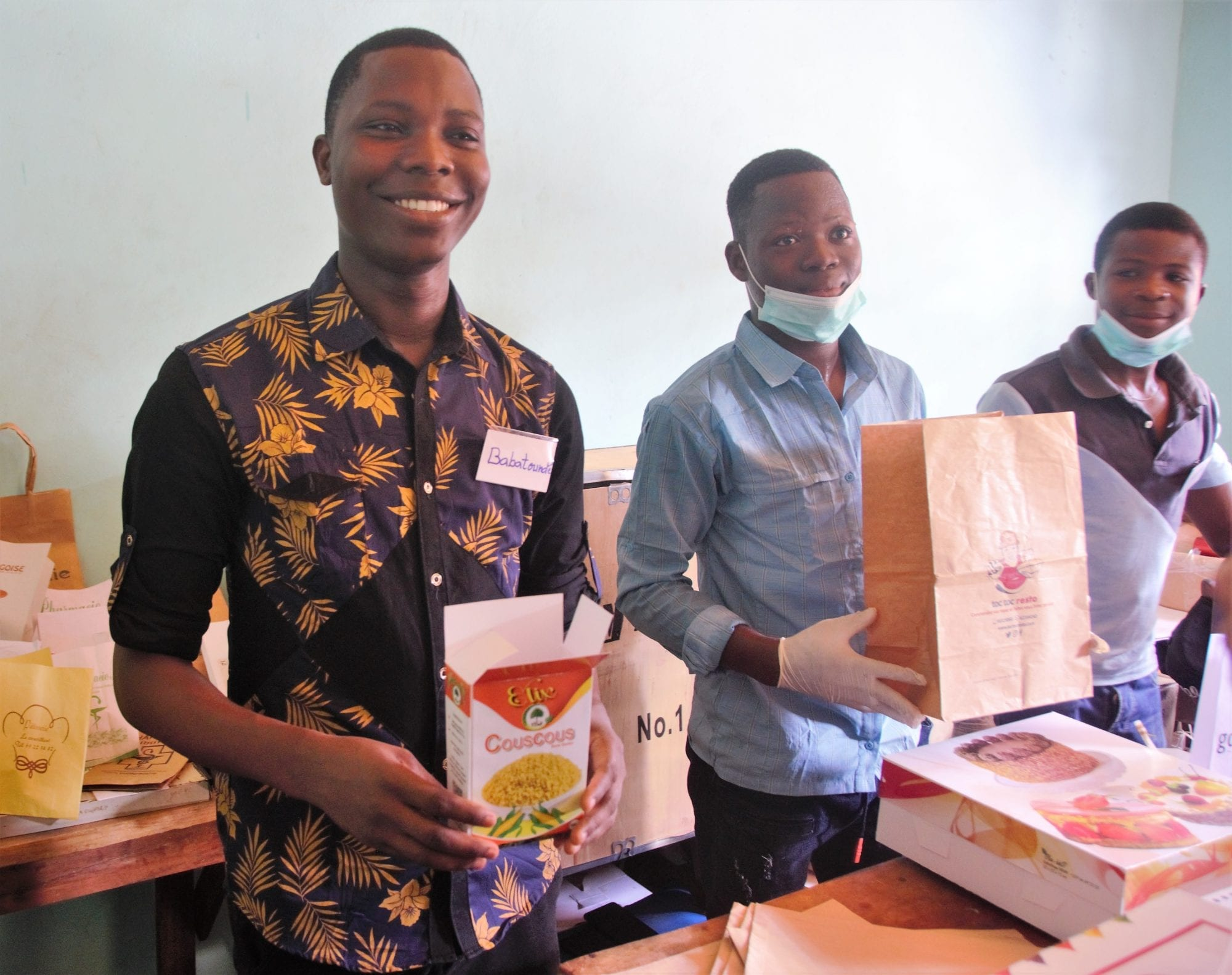 Babatundé Oguidi stands with his colleagues inside his packaging business in Benin