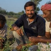 Smiling people inspecting crops