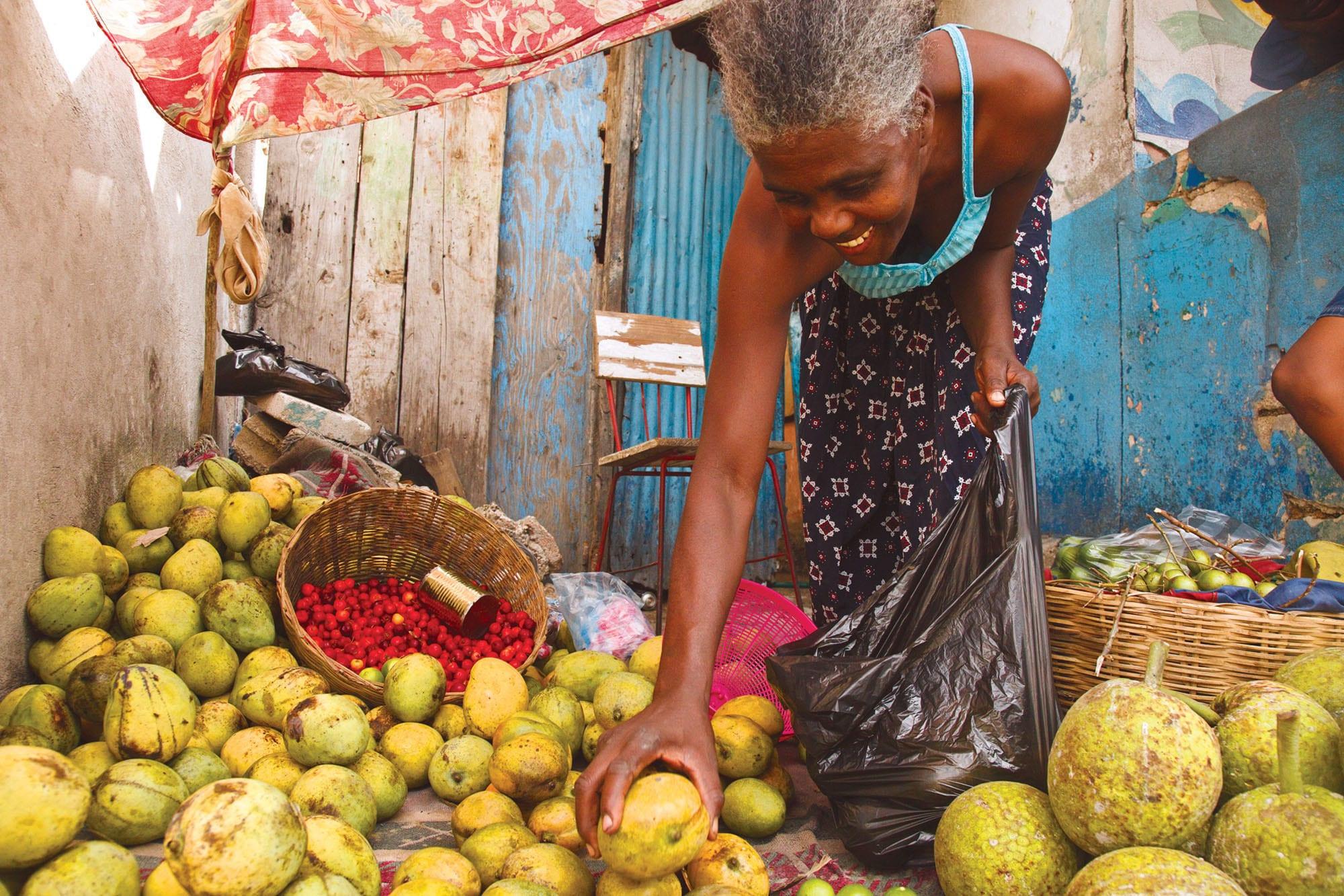 A woman sells mangoes in Haiti