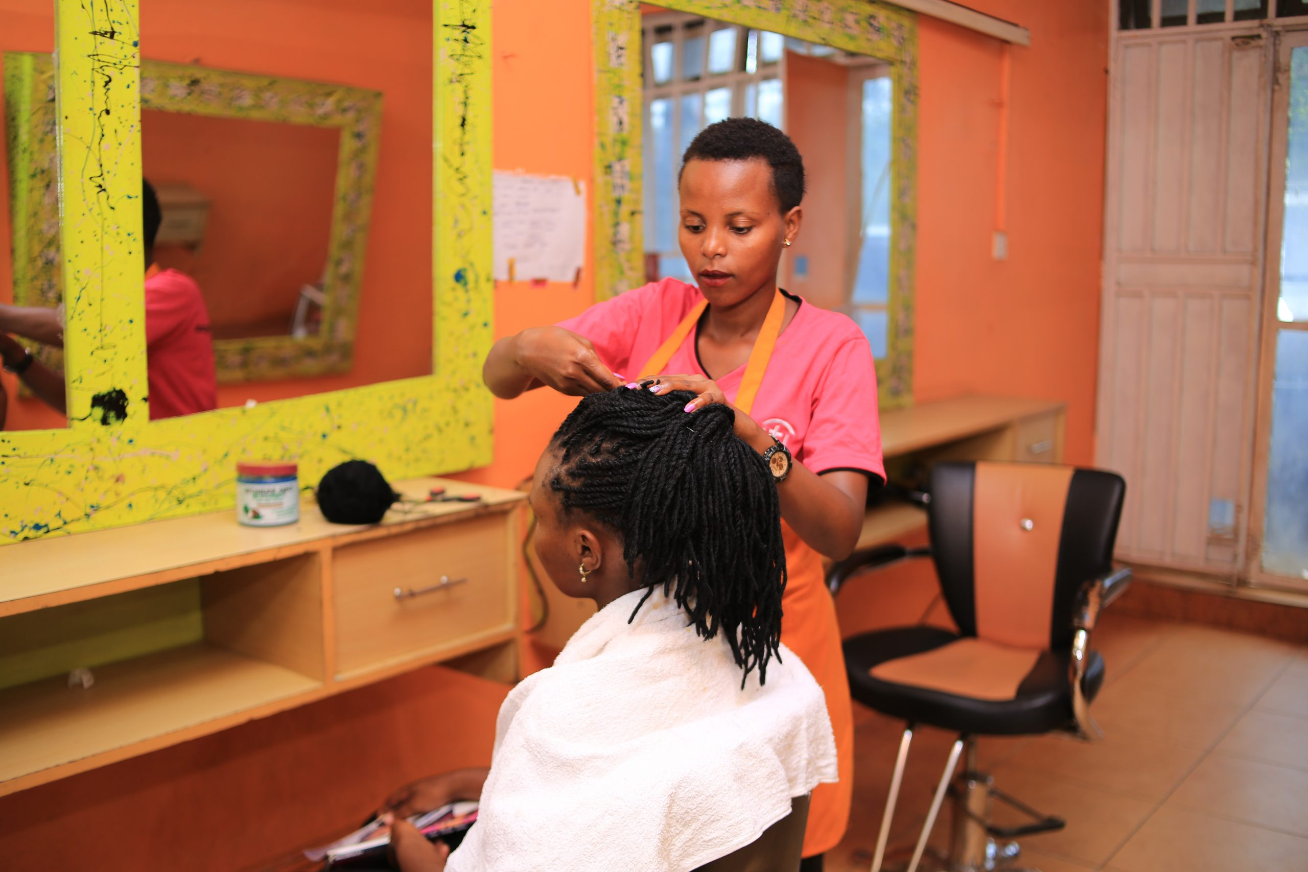 Carolyn works on a client in her salon business near Kampala, Uganda