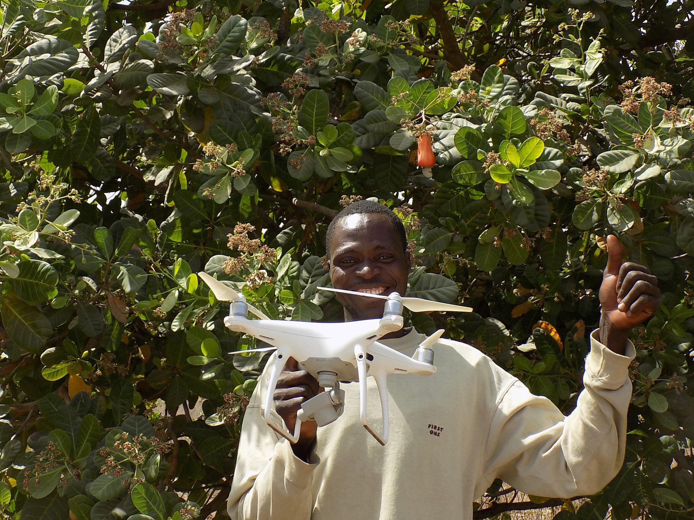 A man holds a drone in a field in Benin