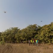 Drones fly over a field in Benin