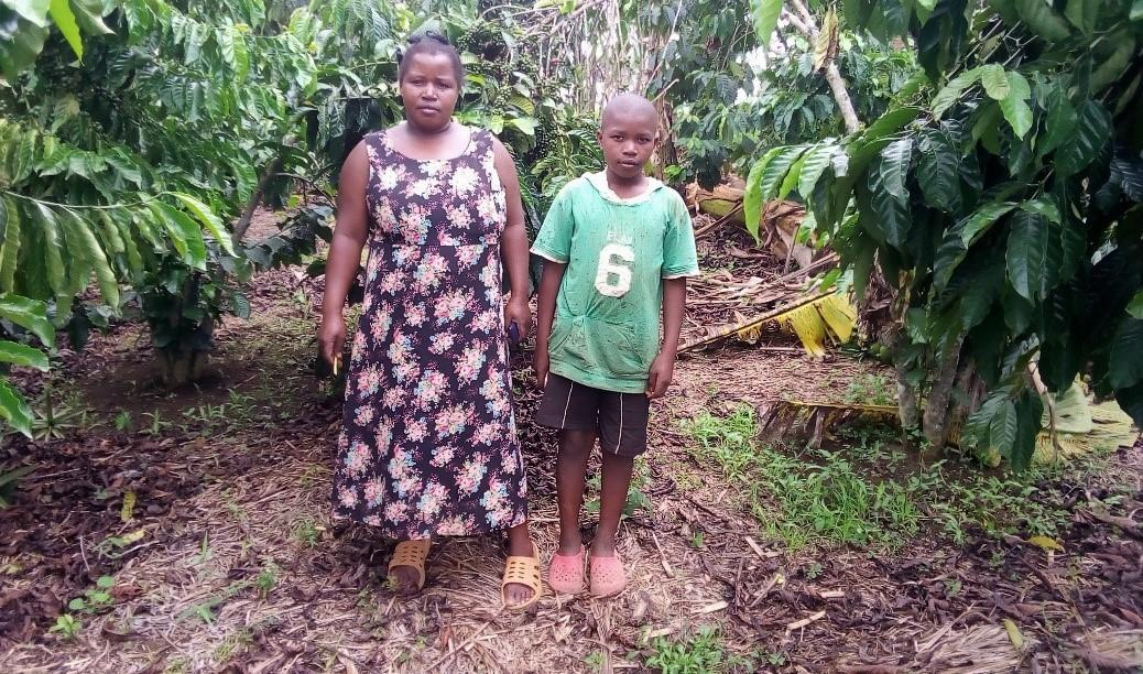 Coffee farmer Ovia Biringwa stands with her son on their farm in Uganda