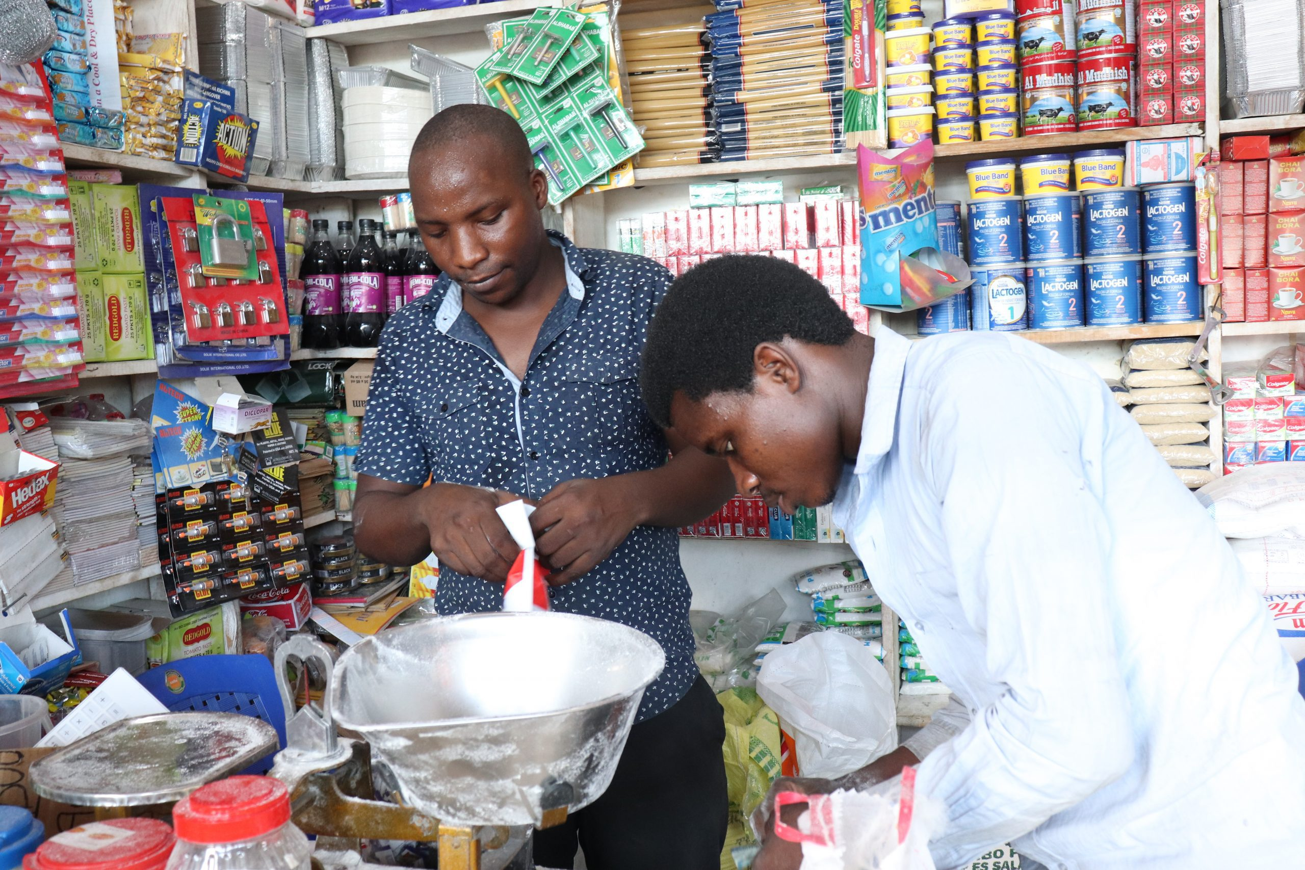 Youth owned shops in Tanzania are valuable opportunities for people like Emanuel Barosha Ndiwene stands in his small shop in Dar es Salaam, Tanzania.