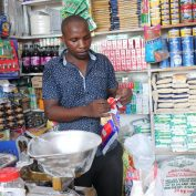 Emanuel Barosha Ndiwene organizes products in his small shop in Dar es Salaam, Tanzania