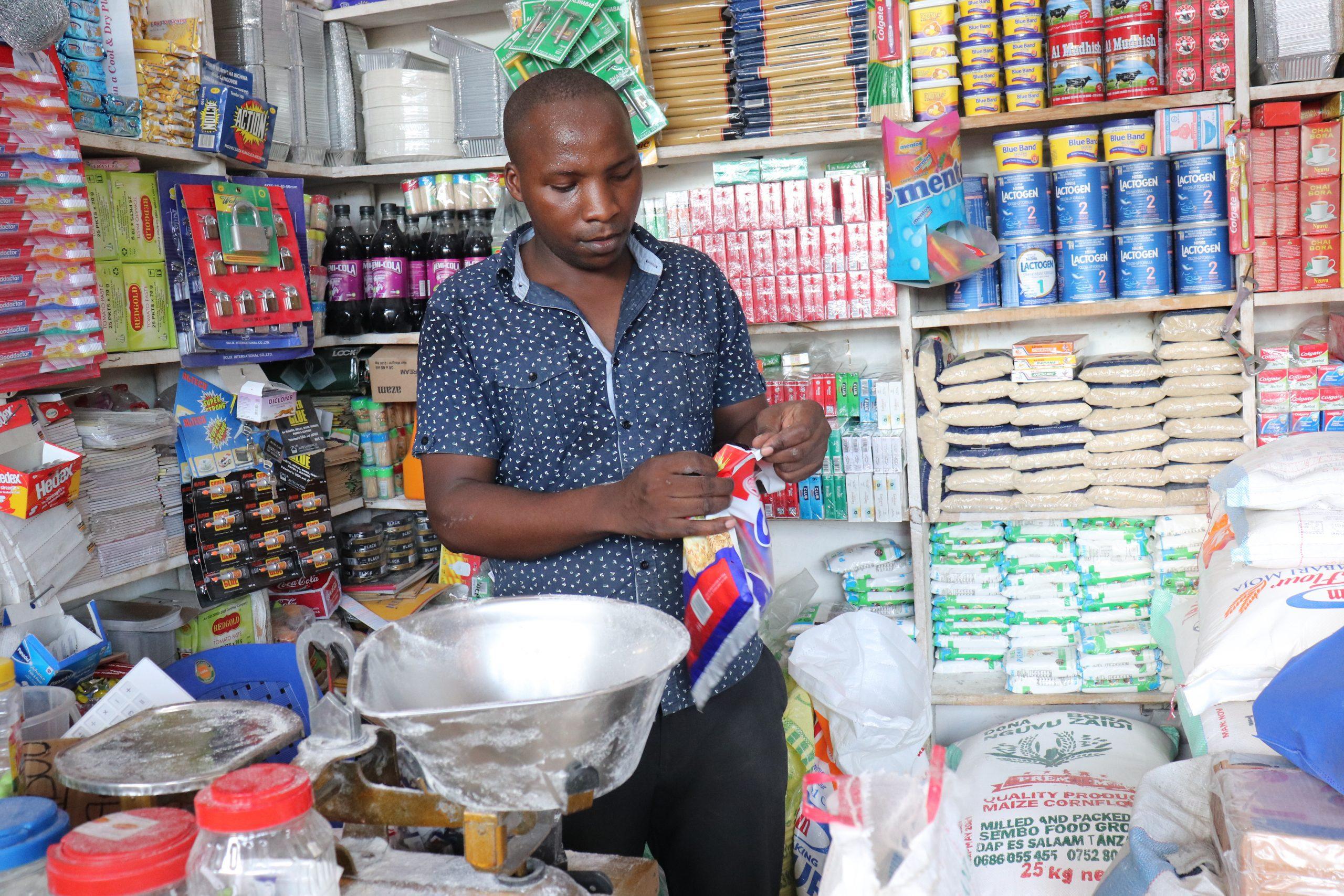 Emanuel Barosha Ndiwene organizes products in his small shop in Dar es Salaam, Tanzania