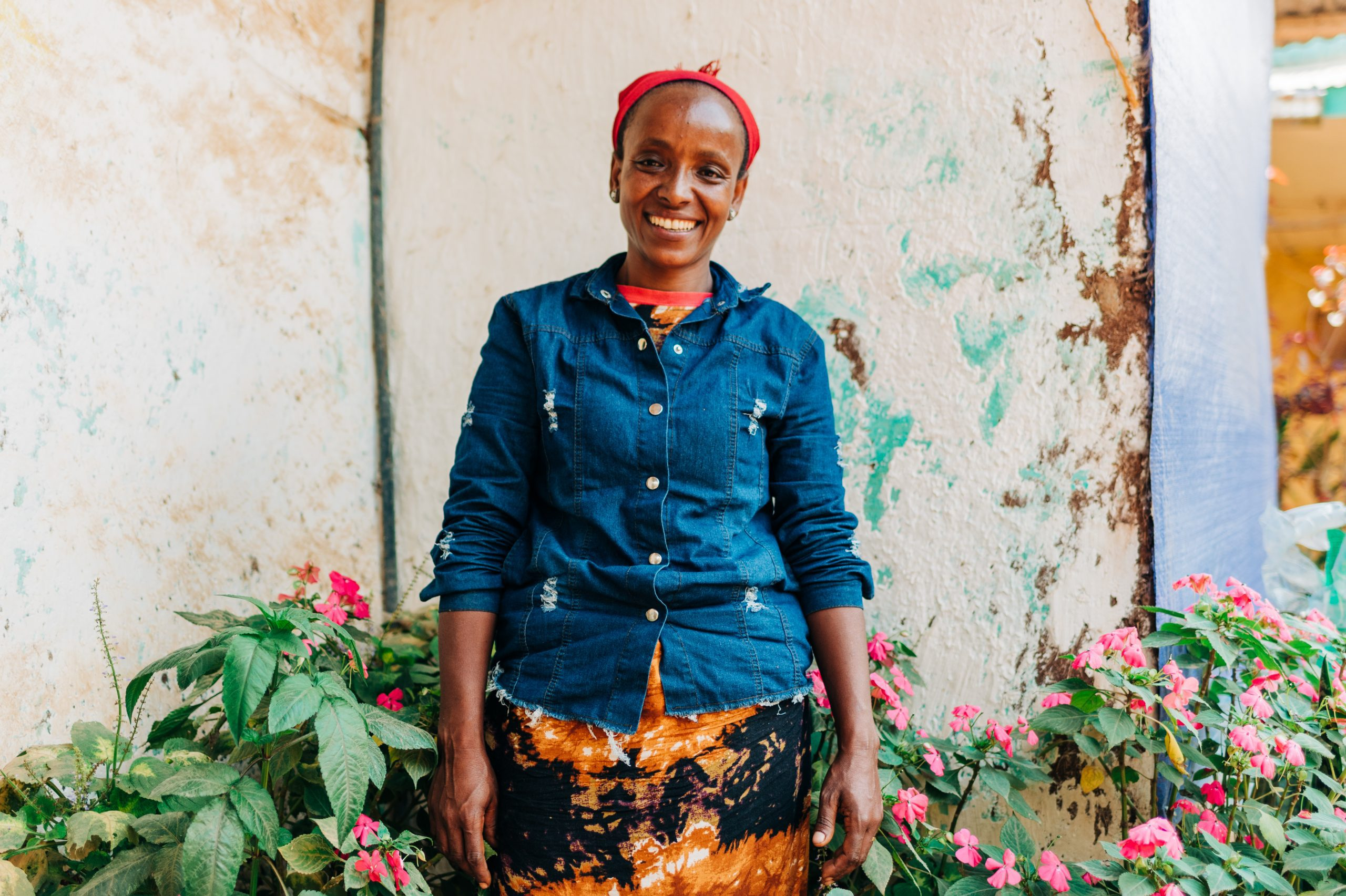 Women Leaders like Lubaba Mekonnen, a coffee farmer in Ethiopia, stands outside her house.