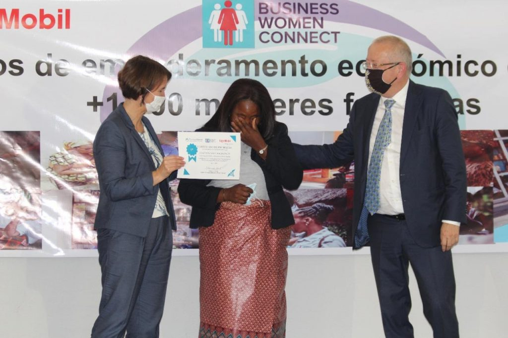 Jane Grob (left) and Jos Evans (right) hand a certificate to the woman entrepreneur who was the winner of the 2021 cohort's business plan competition