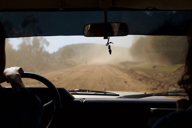 A can drives down a dirt road in rural Ethiopia