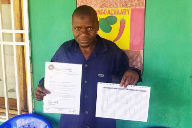 A chili processor in Malawi displays his certificate and income book
