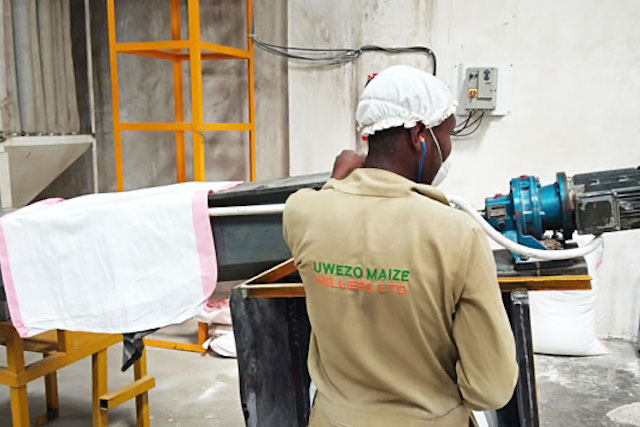 A maize mill operator at Uwezo maize mill oversees the newly installed fortification system