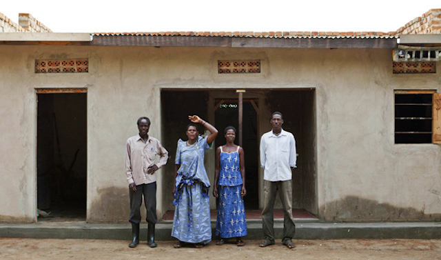 Farmer standing with newly purchased house in result of cotton farming in Uganda