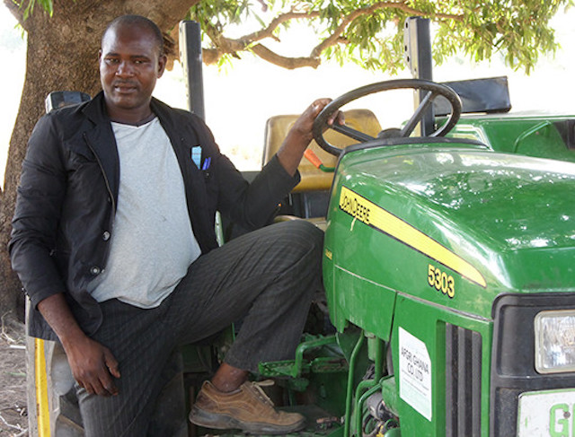 Successful agricultural entrepreneur in Ghana stands by his tractor