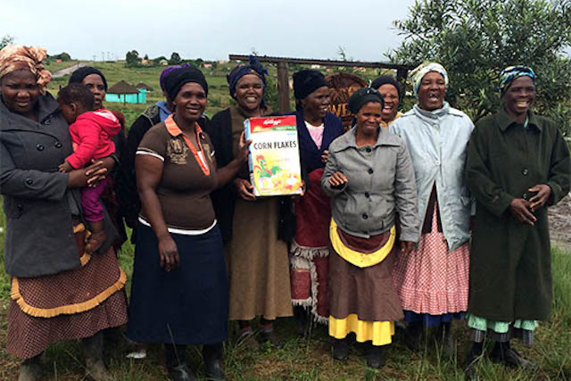 Women farmers holding final product from Kellogs that they helped contribute to produce