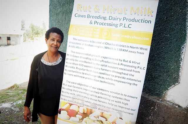 Hirut Yohannes Darare standing next to her dairy product sign in Ethiopia