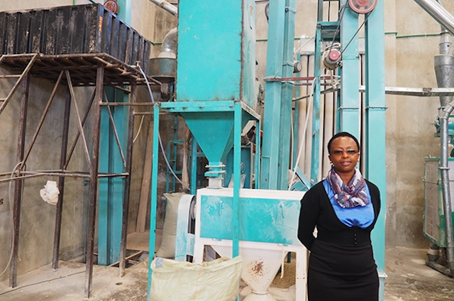 Pauline Kamau standing in-front of manufacturing equipment that she utilizes