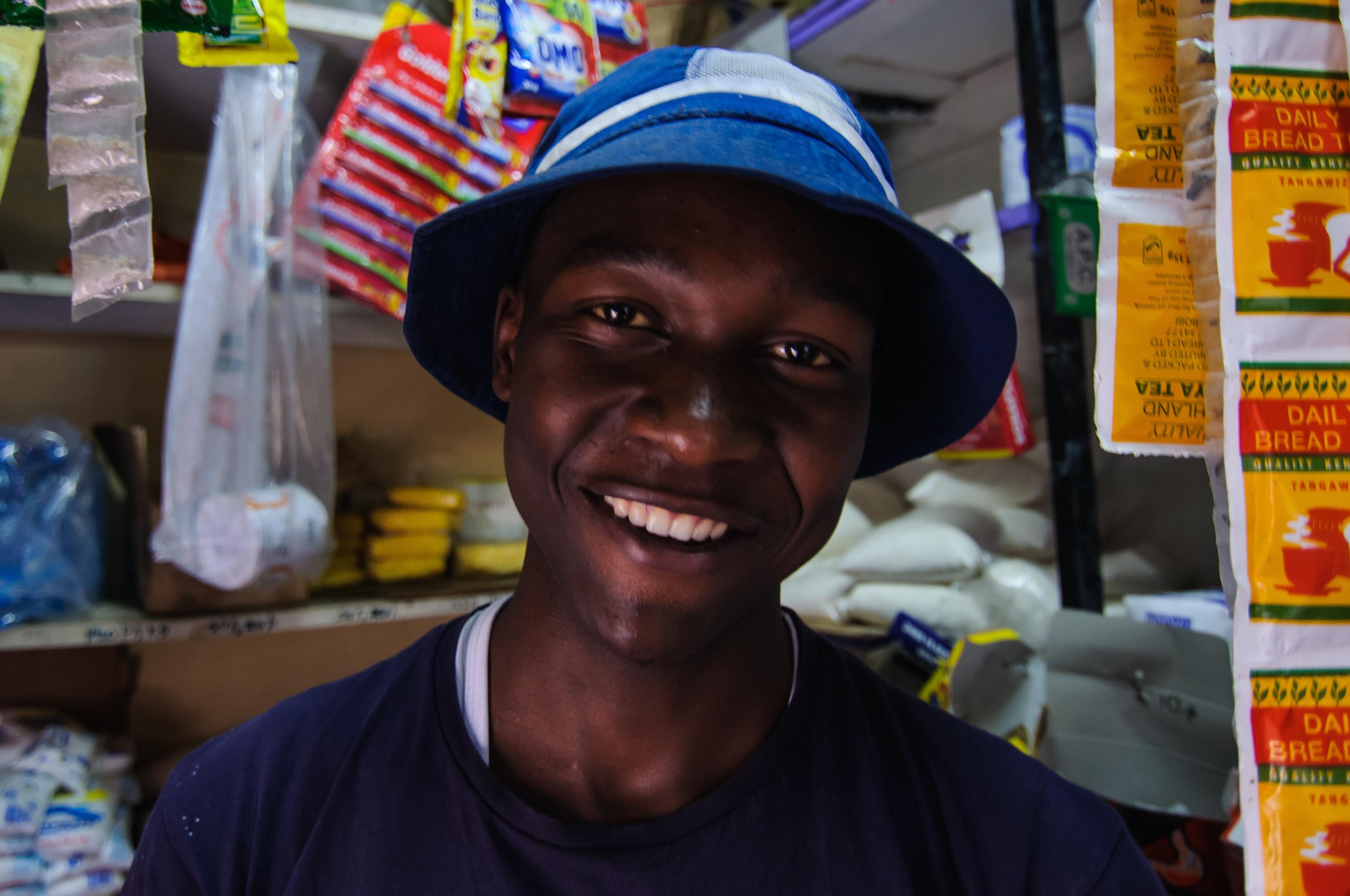 Cosmas Mwangi standing at his shop window in Nairobi