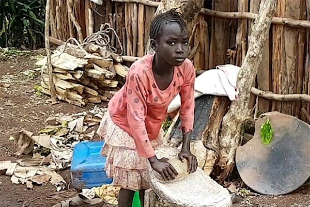 Young girl grinding maize during her daily labor