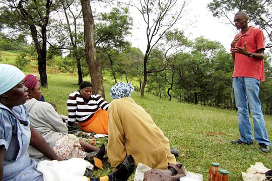 TechnoServe business advisor Musa Maseko teaching financial literacy training to a group of Swazi women
