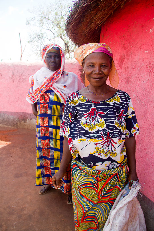 Two women standing next to their homes in Ghana